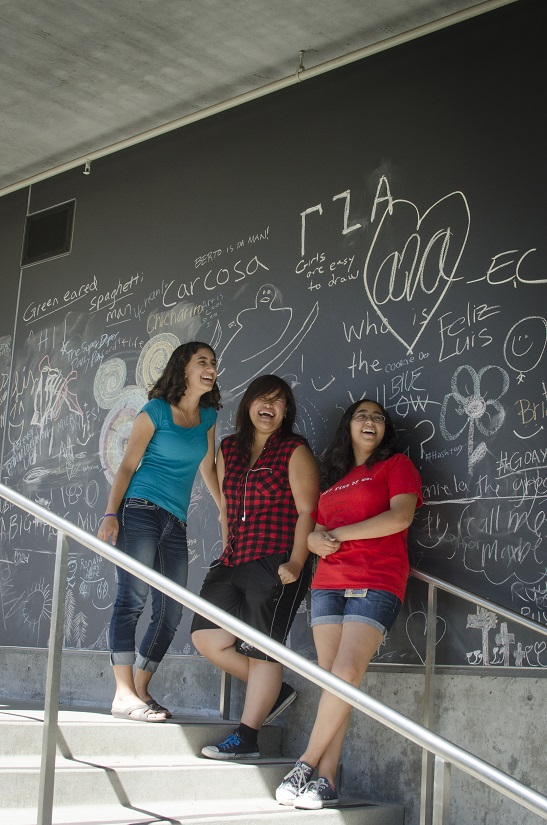 Three students stand on stairs by chalkboard wall.